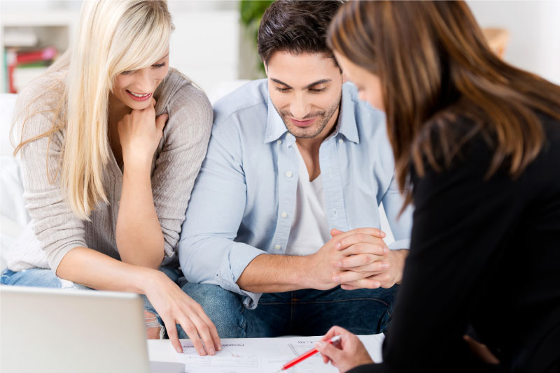 Female financial advisor creating personalized financial plan with young couple.