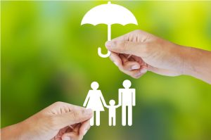 Paper umbrella protecting a paper family